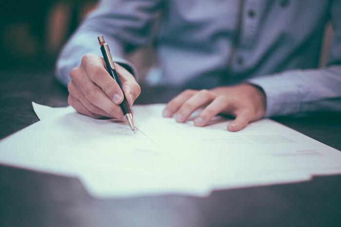 man-sign-contract-pen-desk